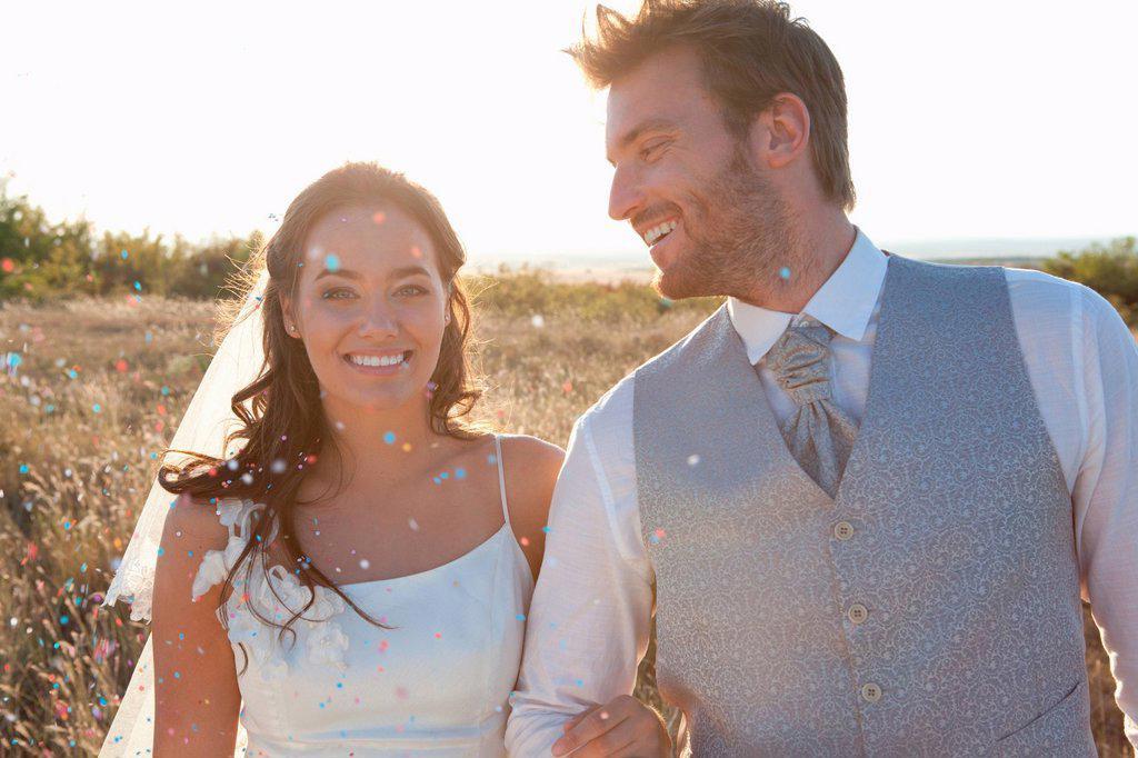Newlywed couple walking in confetti : Stock Photo
