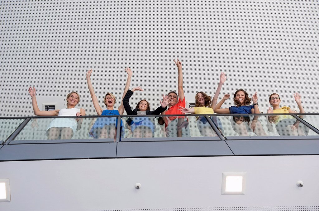 Business people waving from balcony : Stock Photo