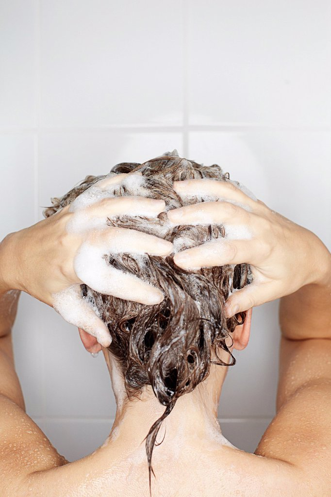Woman washing her hair in shower : Stock Photo