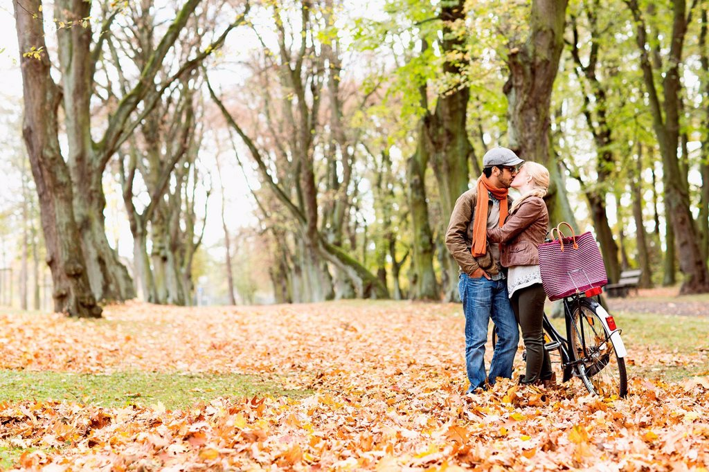 Stock Photo: 1773R-173814 Couple kissing by bicycle in forest