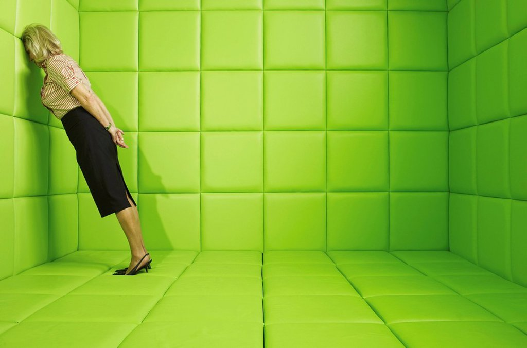 Woman leaning head against wall in a green padded cell : Stock Photo