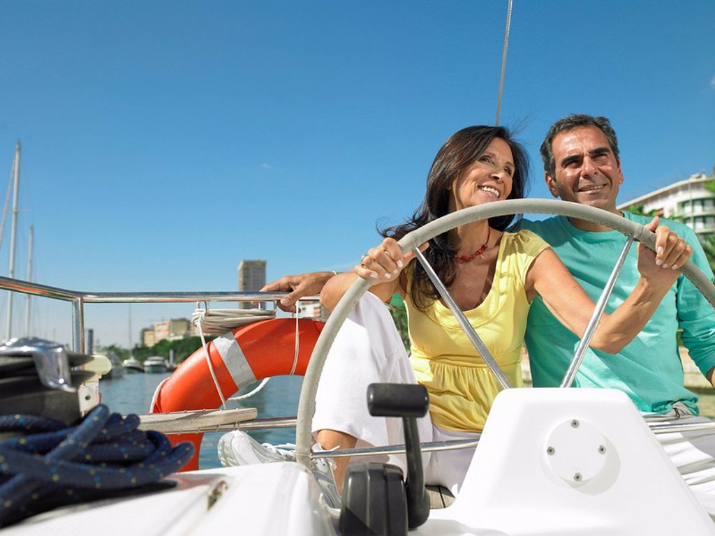 Stock Photo: 1773R-175110 Mature couple at wheel of yacht, smiling