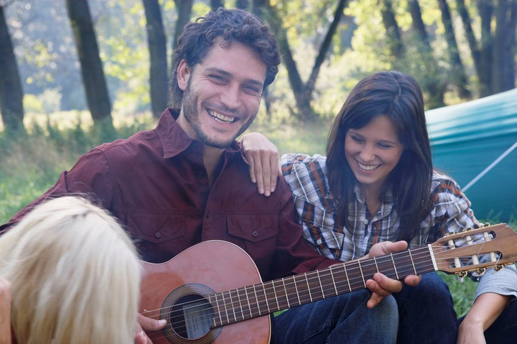 Stock Photo: 1773R-175454 Man at campsite playing guitar with two woman listening and smiling