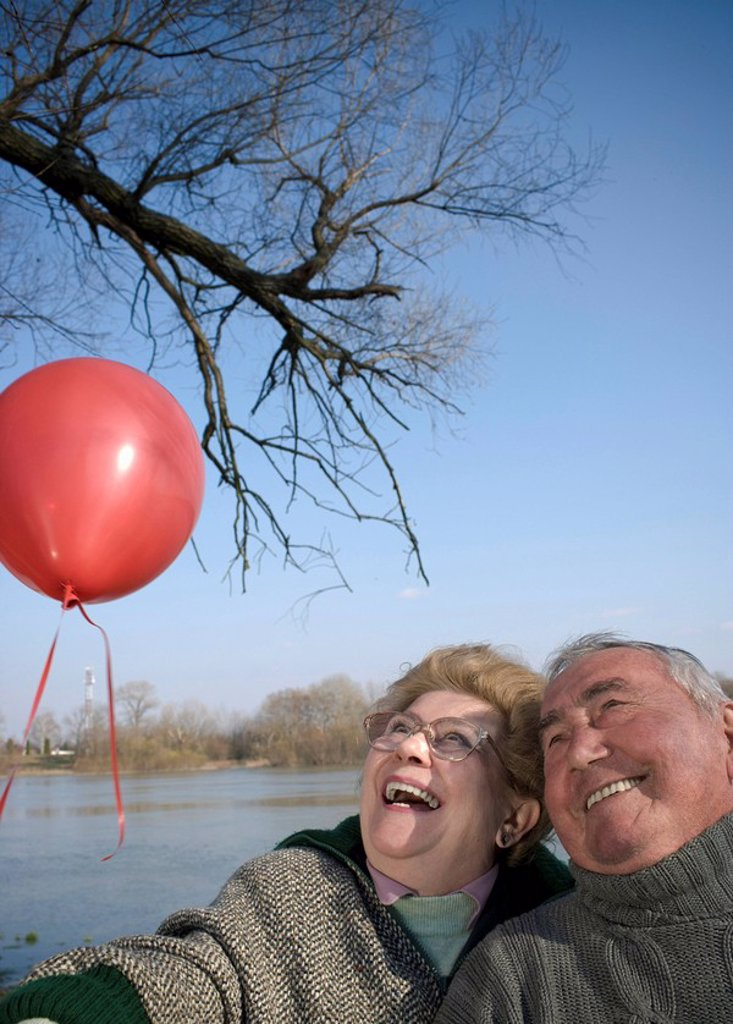Senior couple by river holding red balloon, heads together, smiling : Stock Photo