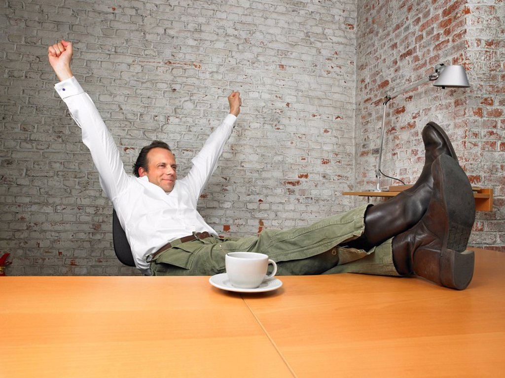 Stock Photo: 1773R-176761 Businessman stretching with feet on desk ,