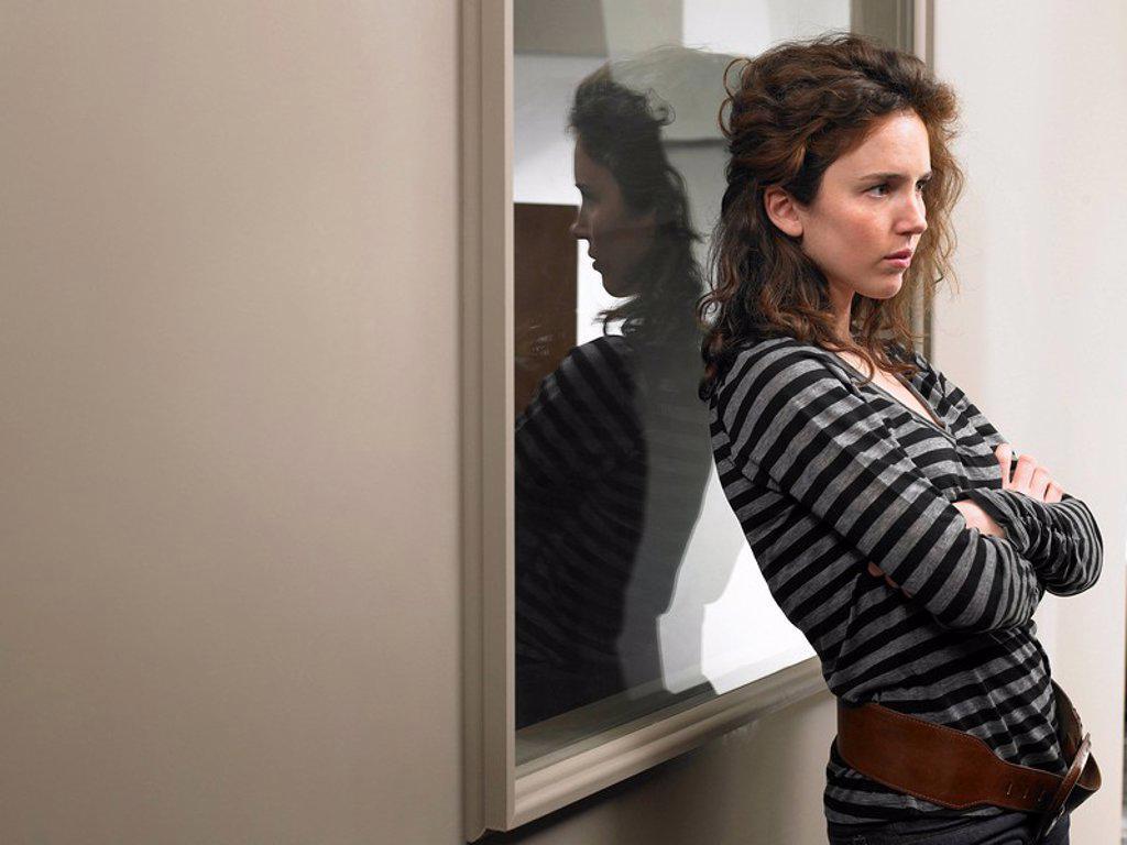 Anxious woman standing in corridor : Stock Photo