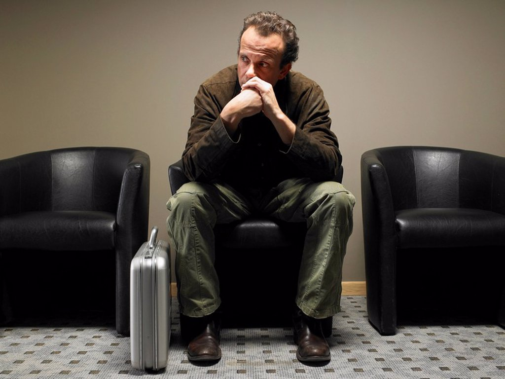 Stock Photo: 1773R-176874 Mature businessman sitting in waiting room, resting chin on hands