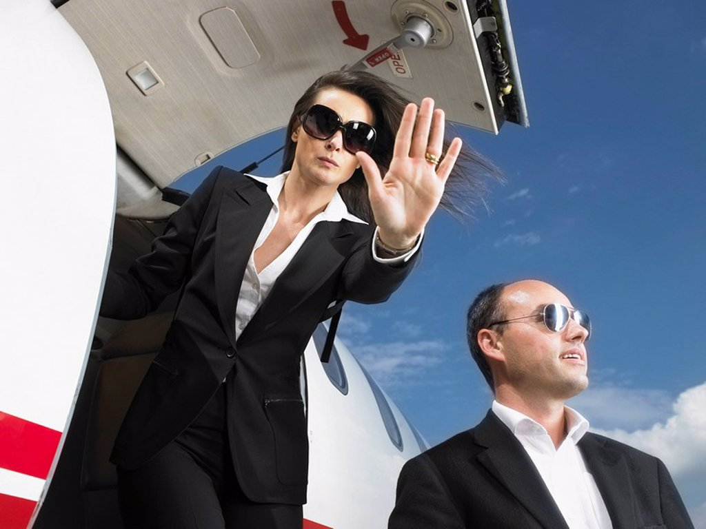 Stock Photo: 1773R-177015 Offensive businesswoman and businessman exiting private jet