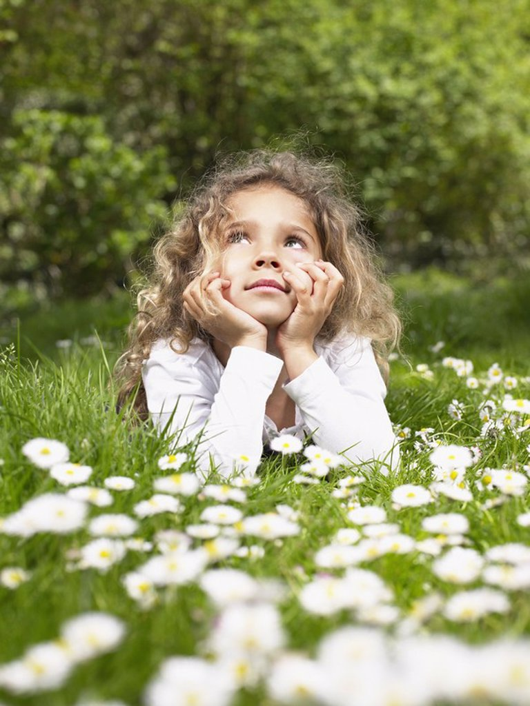 Young girl lying in the grass relaxing : Stock Photo