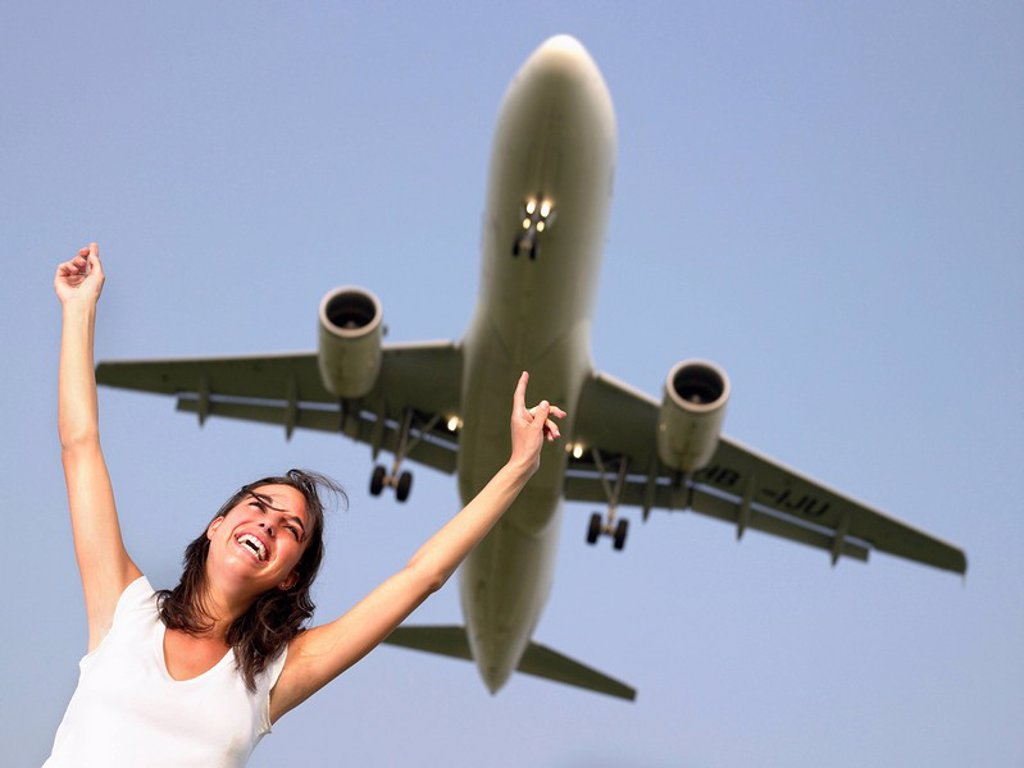 Stock Photo: 1773R-177365 Woman smiling with arms outstretched standing below a plane flying overhead