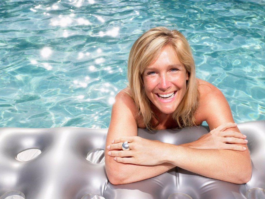 Stock Photo: 1773R-177706 Woman on air mattress in pool