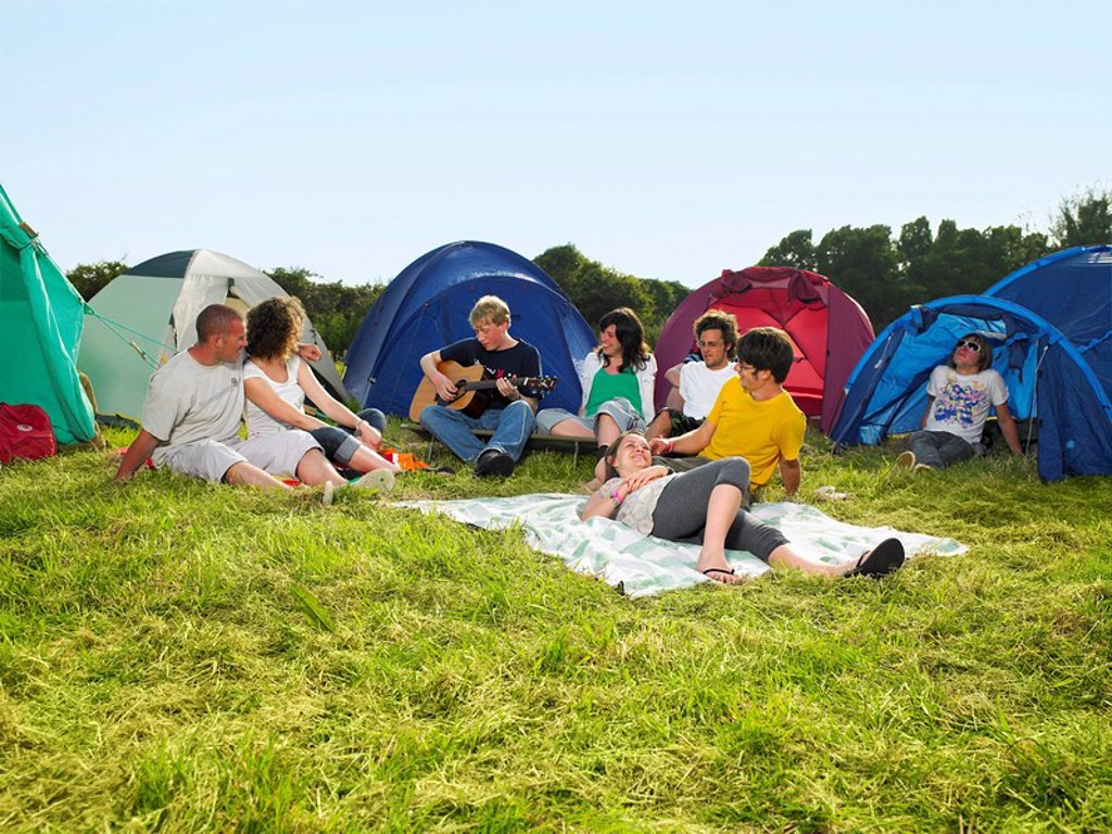 Group sitting outside tents one playing guitar : Stock Photo