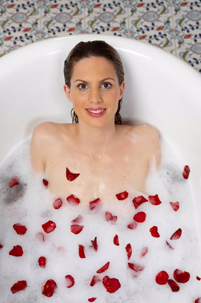 young woman lying in bath with lather and rose petals, overhead view, portrait : Stock Photo