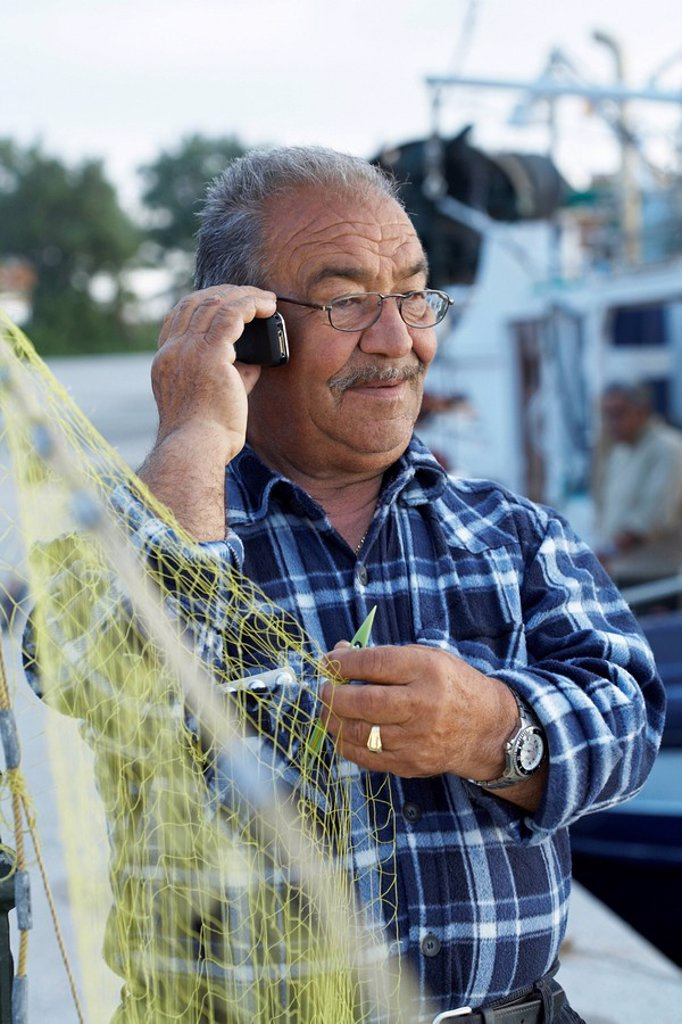 Mature fisherman fixing net while on cell phone : Stock Photo