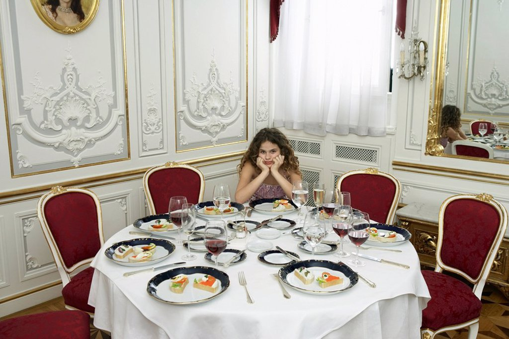 Girl 9-11 sitting on her own at dinner table : Stock Photo