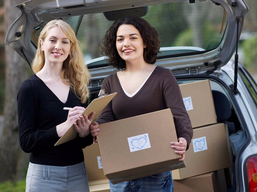 Two women checking boxes at car : Stock Photo