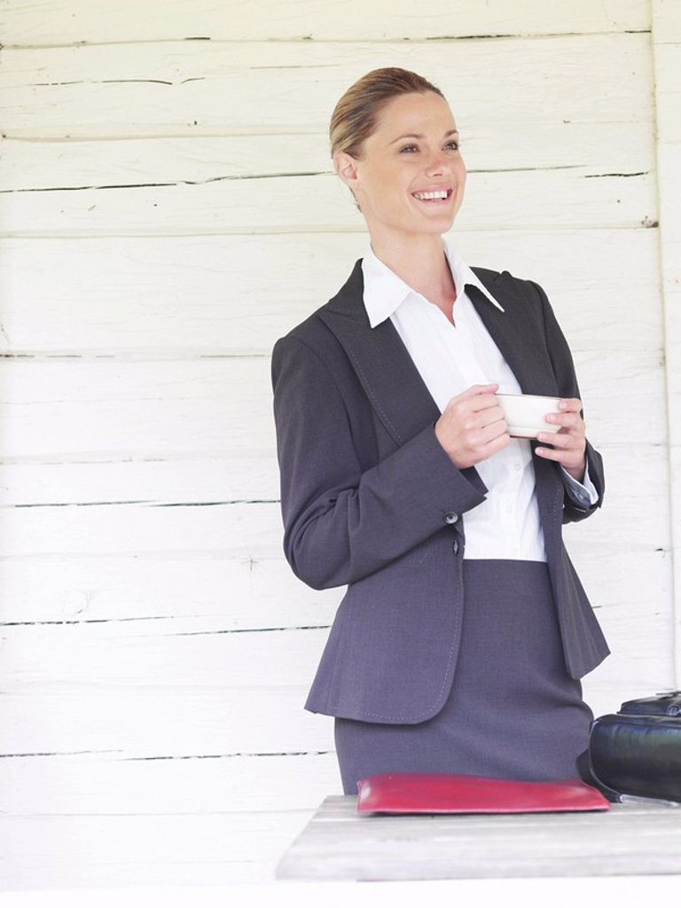 Businesswoman by country cottage with coffee : Stock Photo