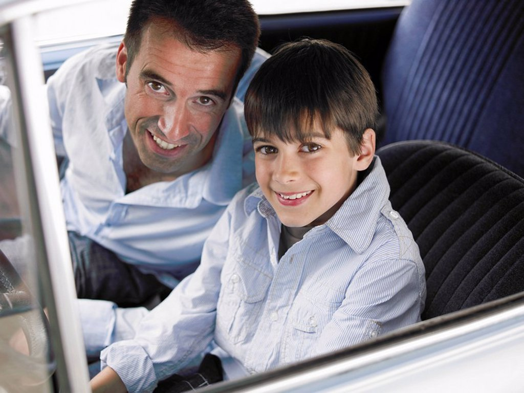 Stock Photo: 1773R-182366 Father and son 8-10 sitting in car, smiling, portrait