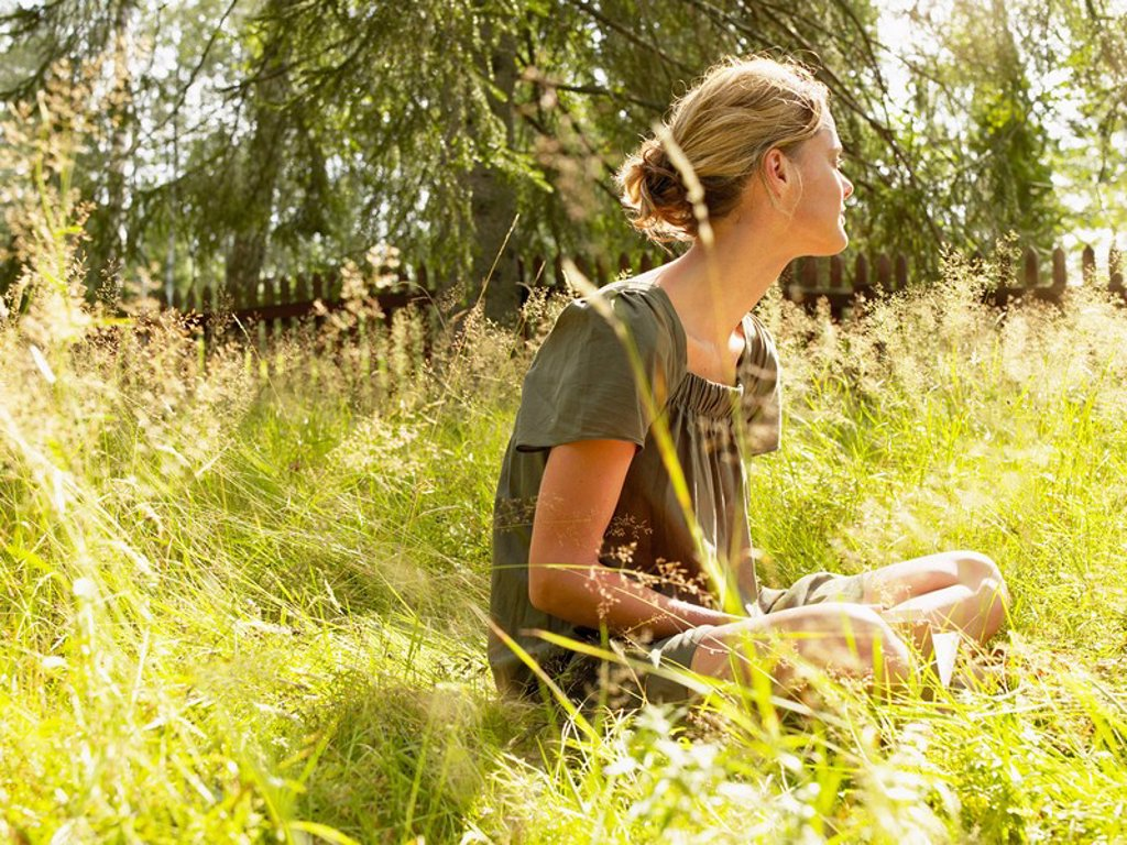 Woman sitting in the grass relaxing : Stock Photo