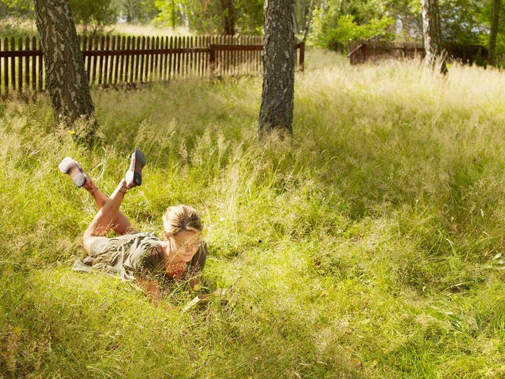 Stock Photo: 1773R-182453 Woman lying in the grass reading