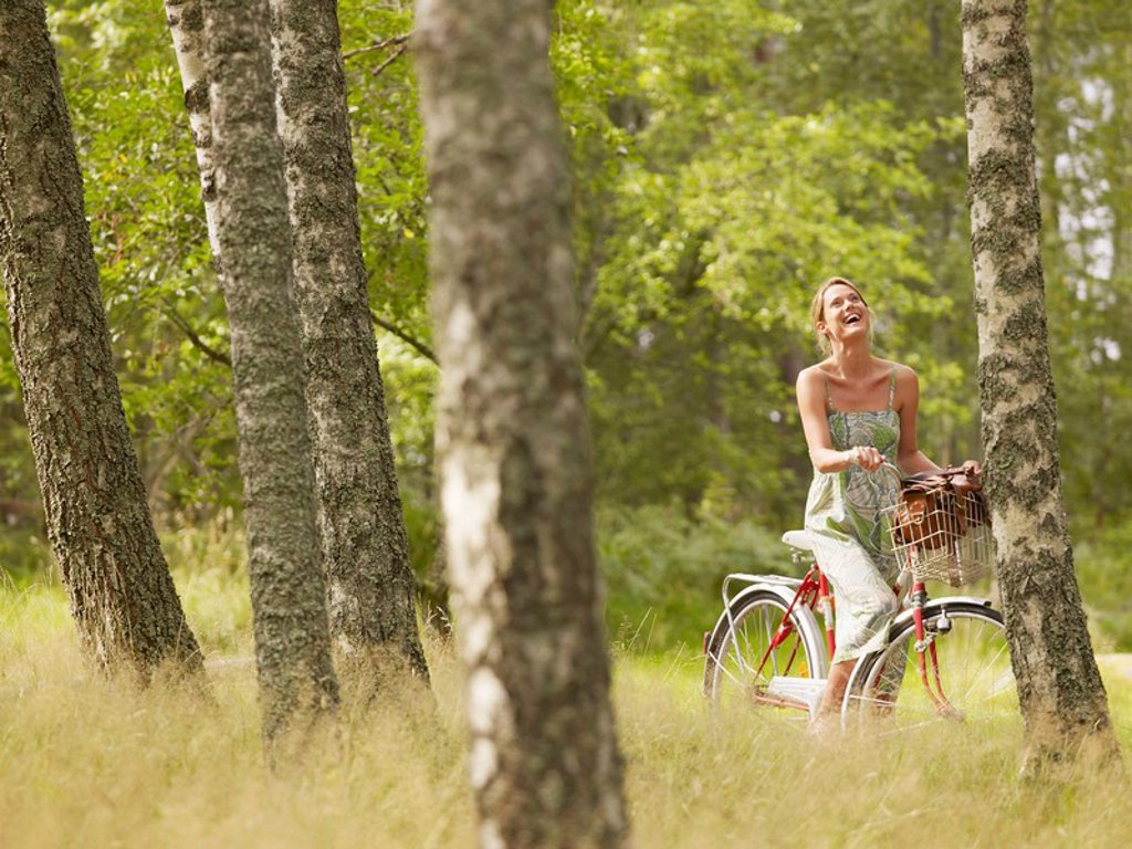 Stock Photo: 1773R-182466 Woman riding a bike in forest smiling