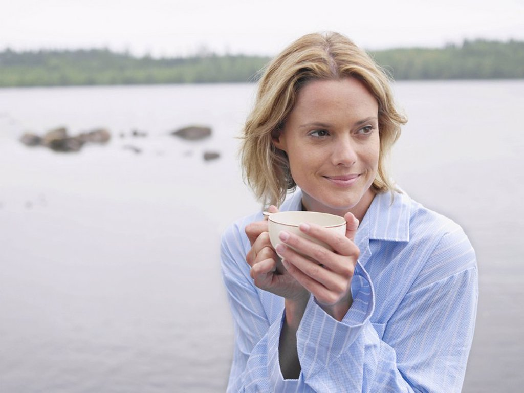 Woman by the water holding a mug : Stock Photo
