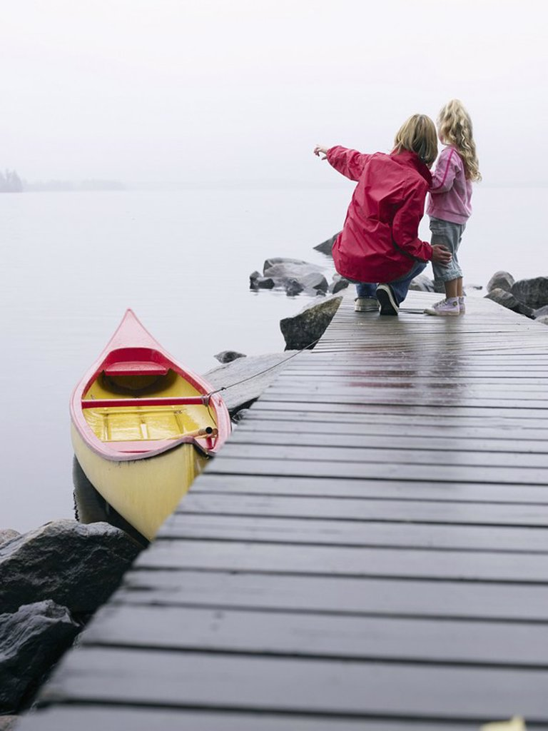 Stock Photo: 1773R-182565 Woman and young girl on a dock near a boat pointing