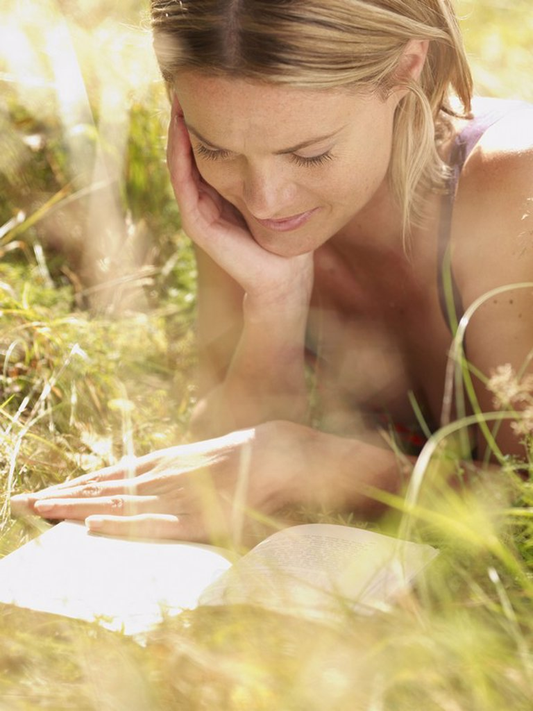 Stock Photo: 1773R-182616 Woman lying in grass reading a book and smiling