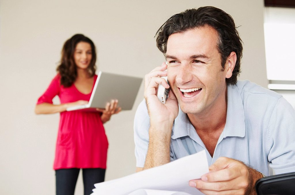 Smiling male on phone with bills : Stock Photo