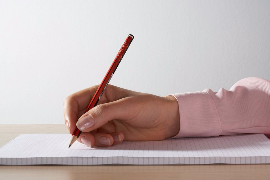 Stock Photo: 1773R-183569 Woman´s hand with a pencil on a pad