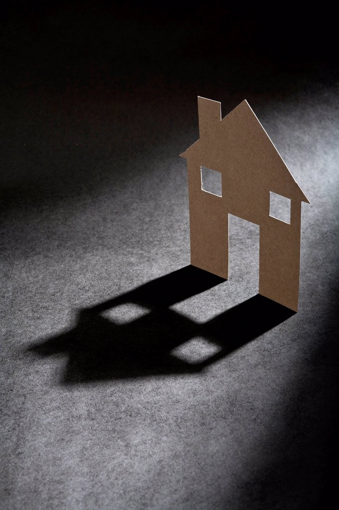 Cardboard house shape casting shadow : Stock Photo