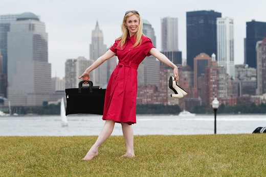 USA, New York City, Woman relaxing in park after work with Manhattan skyline in background : Stock Photo