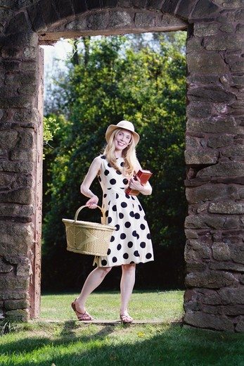 USA, New Jersey, Woman carrying picnic basket and book looking through old barn door and smiling : Stock Photo