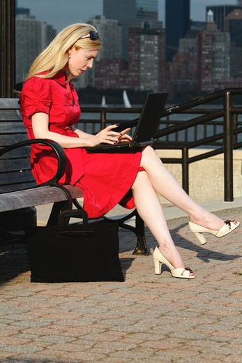 USA, New Jersey, Jersey City, Liberty State Park, Woman in red dress sitting on bench and looking at laptop : Stock Photo