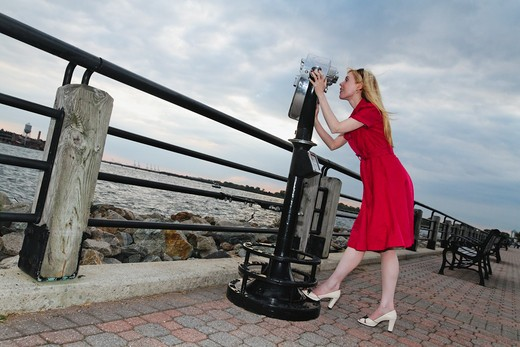Stock Photo: 1774-618 USA, New Jersey, Jersey City, Liberty State Park, Woman in red dress looking through binocular, Low angle view