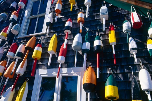 USA, Maine, Colorful lobster buoys hanging on wall of house : Stock Photo