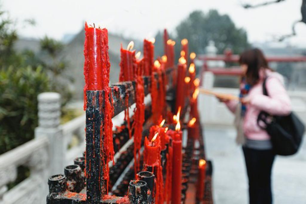 China, Shaanxi, Xian, Woman lighting candle at Big Wild Goose Pagoda : Stock Photo