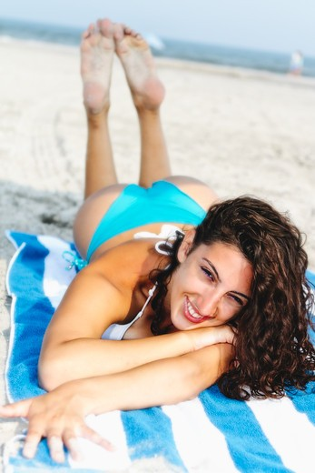 USA, New Jersey, Ocean City, Portrait of smiling Woman in bikini lying on beach : Stock Photo