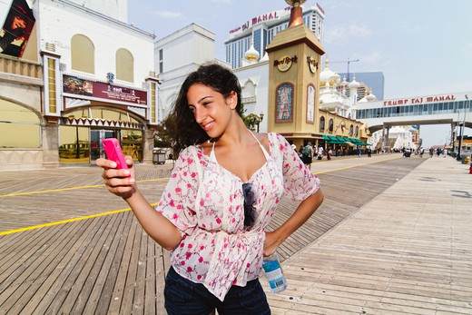 Stock Photo: 1774R-749 USA, New Jersey, Atlantic City, Boardwalk, Woman Checking Messages on Smartphone