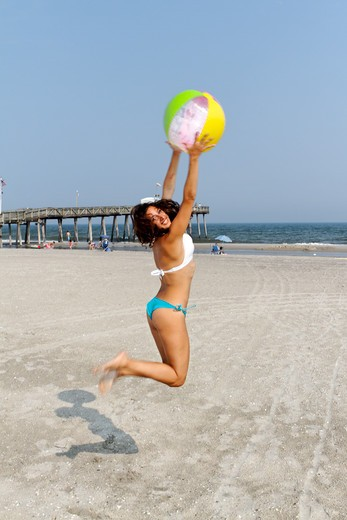 USA, New Jersey, Ocean City, Woman in Bikini Jumping Up to Catch Beach Ball on Beach : Stock Photo