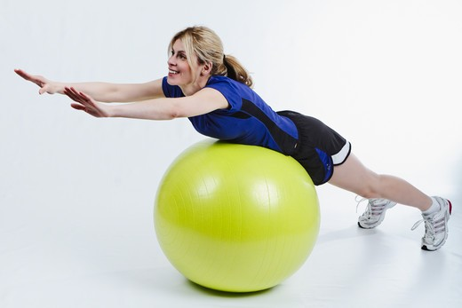 Stock Photo: 1774R-752 Woman Lying on Belly on Exercise Ball and Stretching