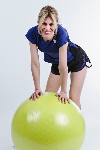 Woman Leaning on Exercise Ball while Working out : Stock Photo