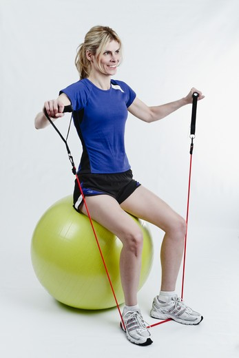 Woman Sitting on Exercise Ball and Pulling Up Exercise Rope : Stock Photo
