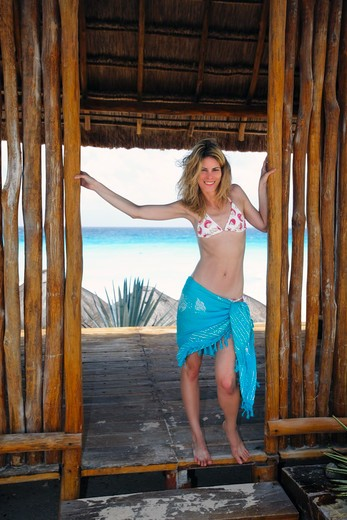 Mexico, Cancun, Young Blonde Woman Standing and Smiling in Entrance of Palapa Hut : Stock Photo