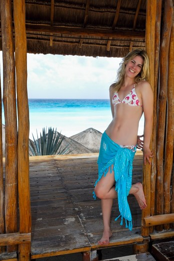 Stock Photo: 1774R-756 Mexico, Cancun, Young Blonde Woman Leaning Against Door of Palapa Hut and Smiling