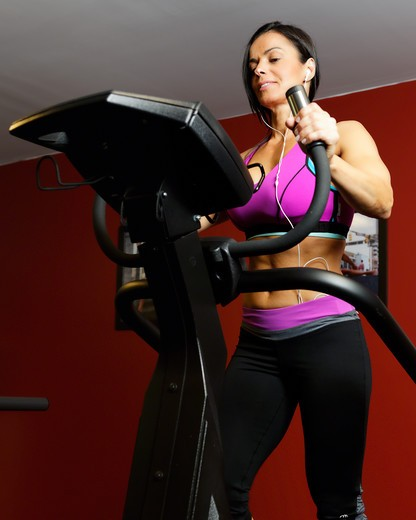 Stock Photo: 1774R-764 USA, New Jersey, Low Angle  View of Fit Woman  Exercisingin  Gym on Cardio Equipment