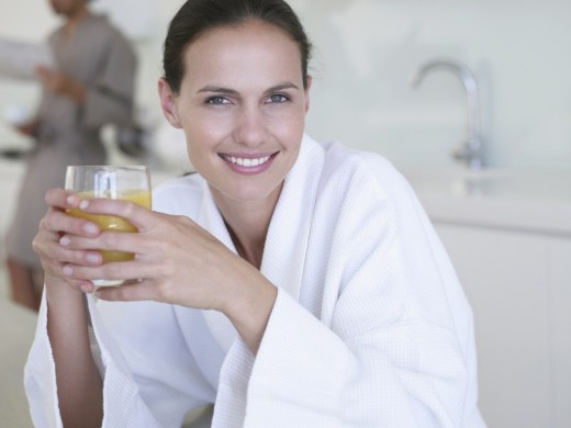 Woman in robe with orange juice and man in background : Stock Photo