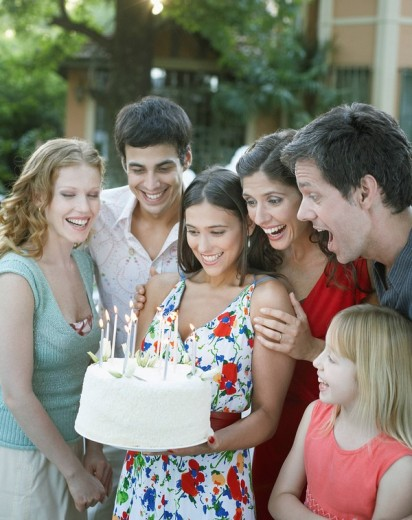 Group of people with birthday cake at a party outdoors smiling : Stock Photo