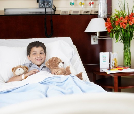 Young boy lying in hospital bed with teddy bears : Stock Photo