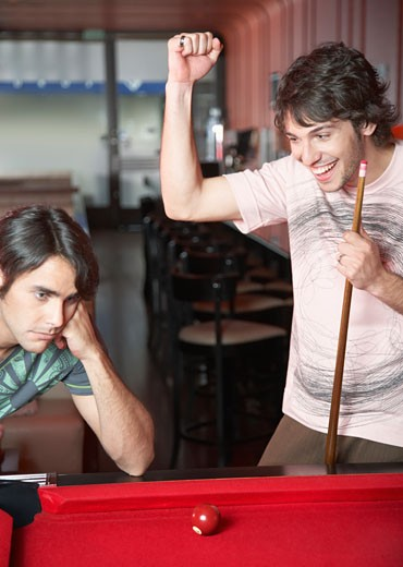 Stock Photo: 1775R-10335 Two men playing pool with one making a winning shot and smiling